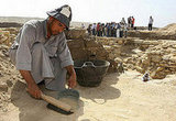 An excavation worker collects sand from the site of an ancient pyramid in Saqqara.
