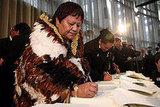 Iwi representatives sign documents.