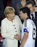 Better luck next time. German Chancellor Angela Merkel shakes hands with German midfielder and captain Michael Ballack.