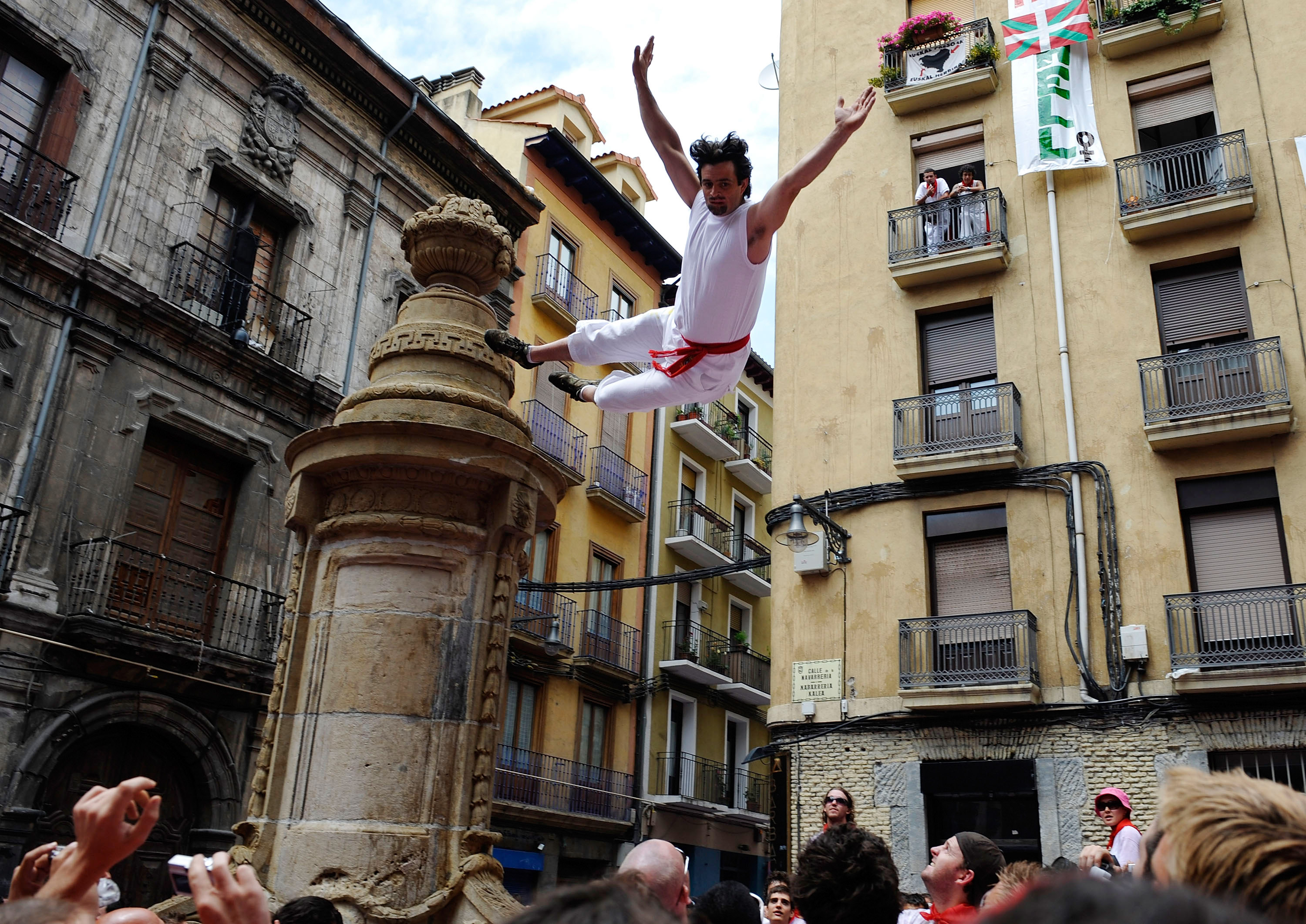 A young reveler jumps from a statue.