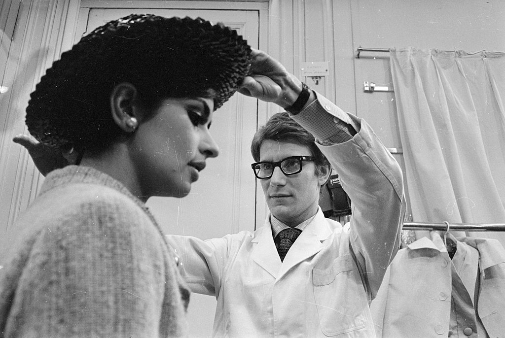 1965: Yves Saint Laurent fits a model at his own fashion house in Paris.
