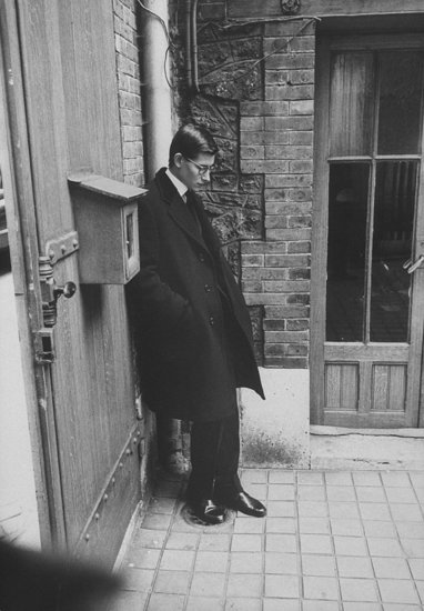 1957: Yves Saint Laurent, successor at Dior, standing alone after Christian Dior's funeral.