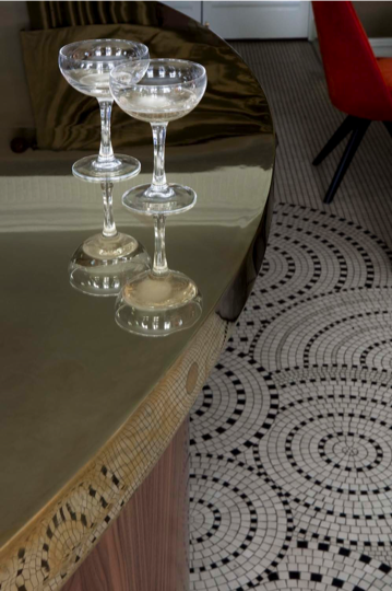 Think shapes. Pairing a curved counter top with the circular patterns on this mosaic floor brings both to the next level. Coordinating shapes of furniture, flooring, and accessories in your home is an easy way to pull it all together.