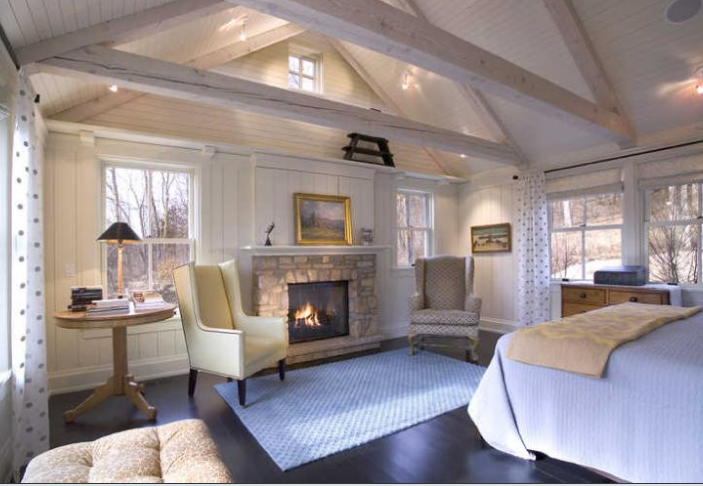 The high ceilings are tempered by whitewashed beams, which help to bring a sense of intimacy to this master bedroom. Simple furnishings, dark-stained maple floorings, and a crackling fire also help to keep the space cozy.
