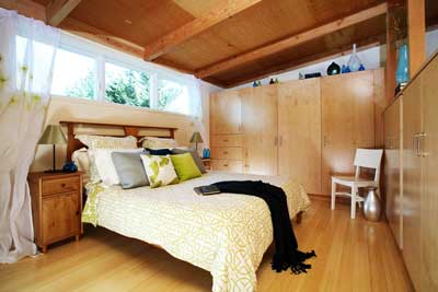 The bedroom features natural sunlight, custom cabinets for smart storage, and bamboo floors.