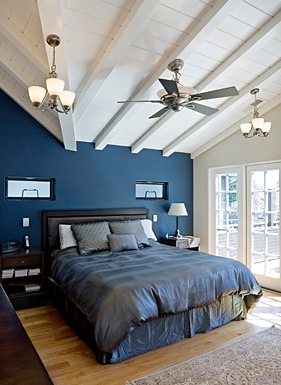 Deep, saturated blues offer a tranquil bedroom space, while soaring white ceilings add elevation.