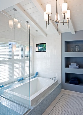 A contemporary chandelier adds a modern element to the open-beamed, whitewashed bathroom ceiling.
