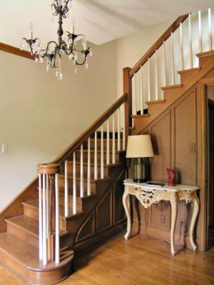 A paneled wall staircase leads from the center hall to the upper floors.