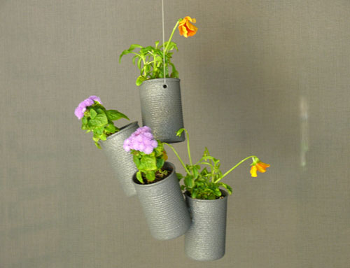 Tin cans hung on a string make cheeky flower planters.