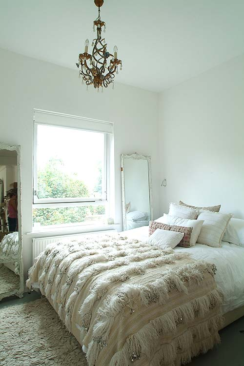 A Moroccan wedding blanket with hand-sewn sequins and a crystal chandelier add glamour to this bleached bedroom.
