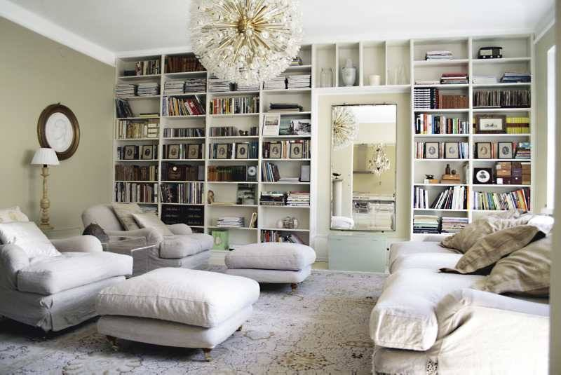 An antique mirror set inside the built-in bookshelves reflects this living room's beautiful mid-century chandelier. Simple linen upholstery and a matching rug keep things calm.