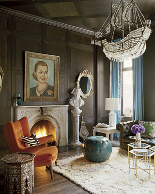 In this living room, Nanette showcases a mix of mid-century (Hans Wegner chair), flea market finds (painting), and vintage (cocktail tables), with eccentric items like a ship-shaped chandelier, sailor bust, and leather pouf.