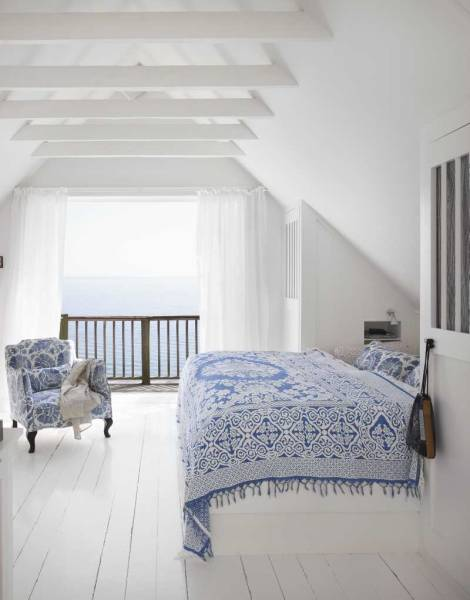 Blue and white textiles pick up the colors in the ocean view. Nightstands recessed into the wall and a bed fit into the sloping ceiling makes great use of the oddly-shaped attic bedroom.
