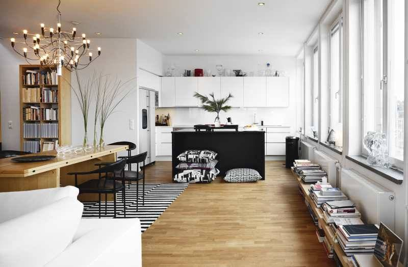 With an open plan design, Färdig's living room is connected to his stylish, custom kitchen. White walls, glossy finishes, and a wall full of windows make the vast space feel open, airy, and larger than it is. The black and white striped Ikea Stockholm Rand ($179) rug coordinates well with the stack of Design House Stockholm Art Pillows ($55).