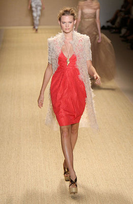 This tailored coral-colored numero topped with a flowing feathered coat has an elegant tropical feel.
