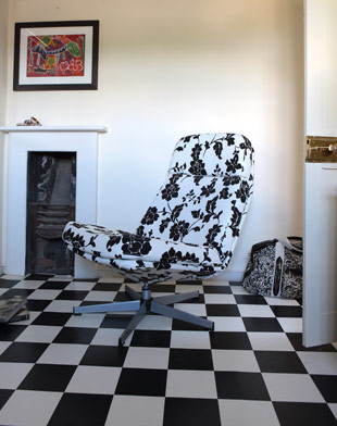 A modern chair upholstered in black and white, like the room's floor tiles, keeps things playful.