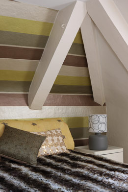 A wall of horizontal stripes serves as focal point and headboard alternative in this bedroom.