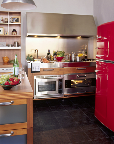 The fiery red shade of this fridge is a great choice for this dynamic kitchen, which is set up for professional cooking. The silver stove, range hood, and pendant shade offset the bright red.