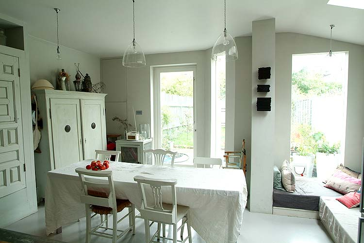 The light shining in from the garden, glass pendants, and white tablecloth and chairs keep this kitchen luminous.