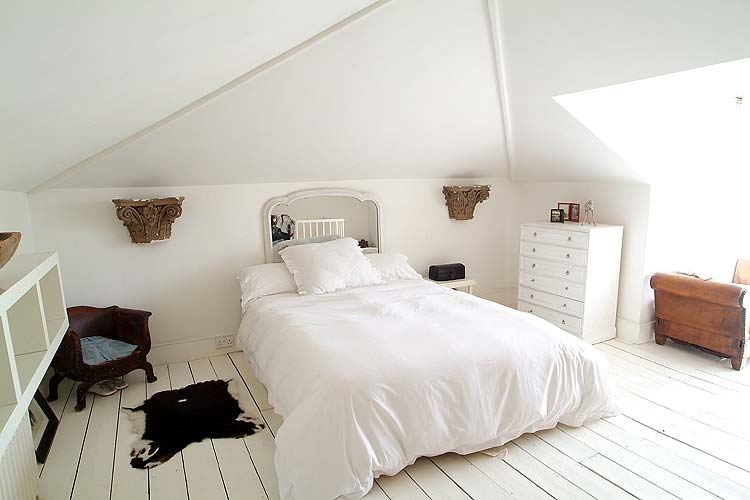 The gabled shape of this bedroom ceiling might feel cramped if a busy wallpaper or dark wall color were used, but white gives it an open, airy feeling.
