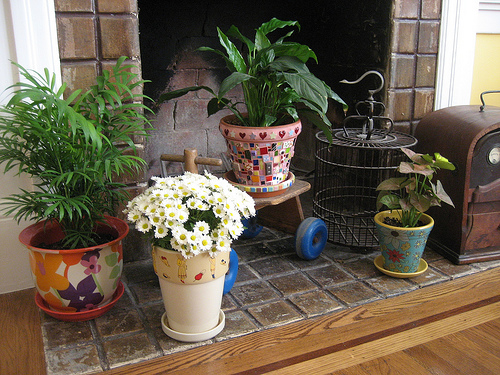 In the warmer months, plants decorate the fireplace. Laurel crafted the mosaic on the middle terra cotta pot. You can see more of her art here.