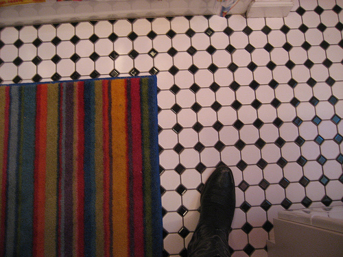 In the bathroom, the black-and-white-patterned floor matches the kitchen floor, though in a smaller pattern.