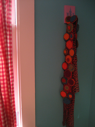 A scarf on the wall adds an interesting contrasting pattern to the gingham curtains.