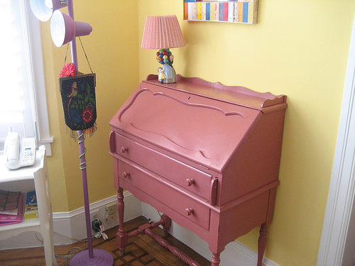 A pink secretary desk offers storage in the living room, while a purple floor lamp, decorated with a vintage beaded bag, adds visual and color interest. Laurel loves searching the Alameda Flea Market as well as vintage shops and garage sales for unique finds.