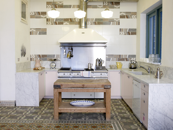This kitchen may have all the essentials (lots of counter space, professional stovetop, island), but the marbled cabinetry and neatly arranged tiles are what attracts me.