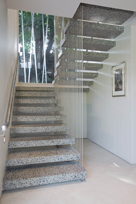 A floating staircase, with its neutral colors, highlights the greenery outside the window.