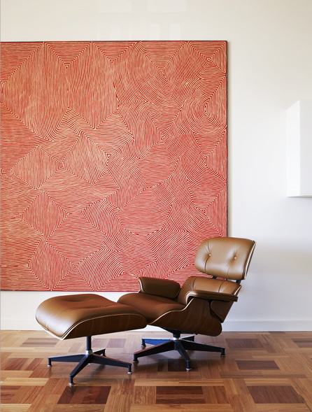 An Eames lounger and ottoman rest on a gorgeous parquet floor. A huge canvas dominates one wall.