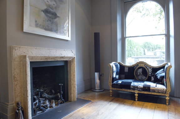 The minimalist fireplace juxtaposes the ornate and eclectic sofa.