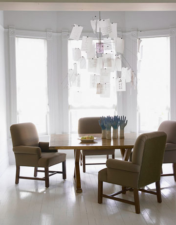 An Ingo Maurer chandelier made of love letters in various languages adds conversation to an empty dinner table.