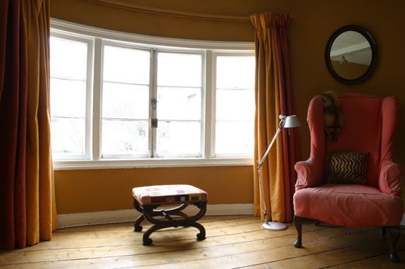 Full-length, heavy drapes extend the lines of the room, while the worn pink wingback adds a charming granny-style touch.
