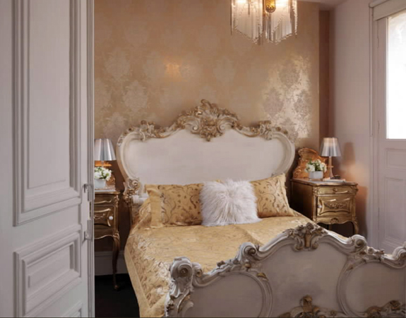 Metallic wallpaper and a Rococo-style bed frame are definitely feminine.
