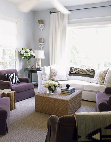 Soft purple upholstery resonates with subtle gray walls, and a sisal carpet brings a natural look to the room.