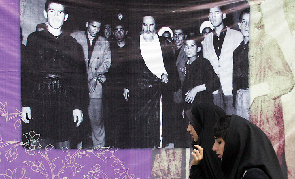Iranian woman walks past a poster showing the late founder of the Islamic Revolution Ayatollah Ruhollah Khomeini addressing supporters.