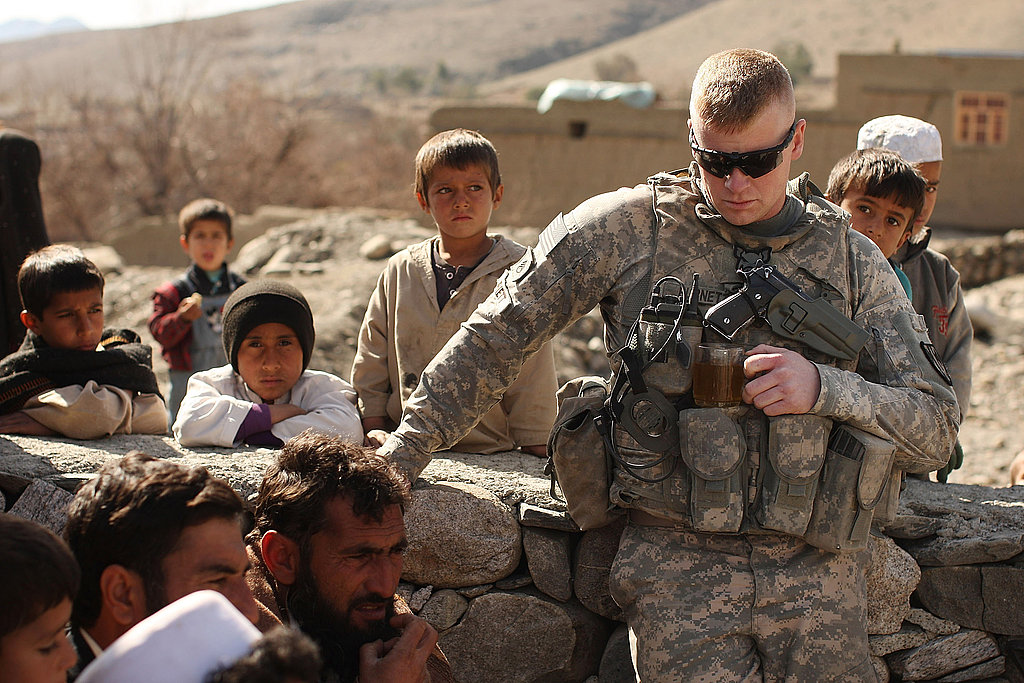 Staff Sgt. Brian Burnett of the US Army 2nd Squad 1st Platoon 527 MP Company sits with villagers.