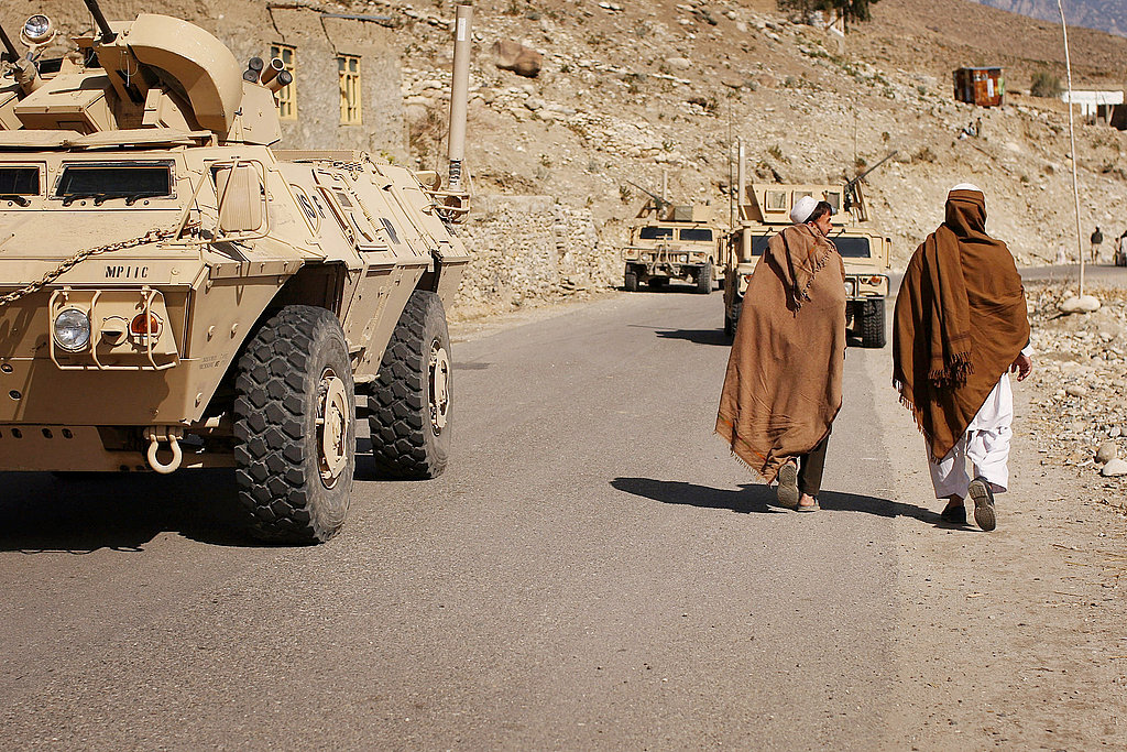 Villagers walk past US military vehicles which are in the area to search for caves.