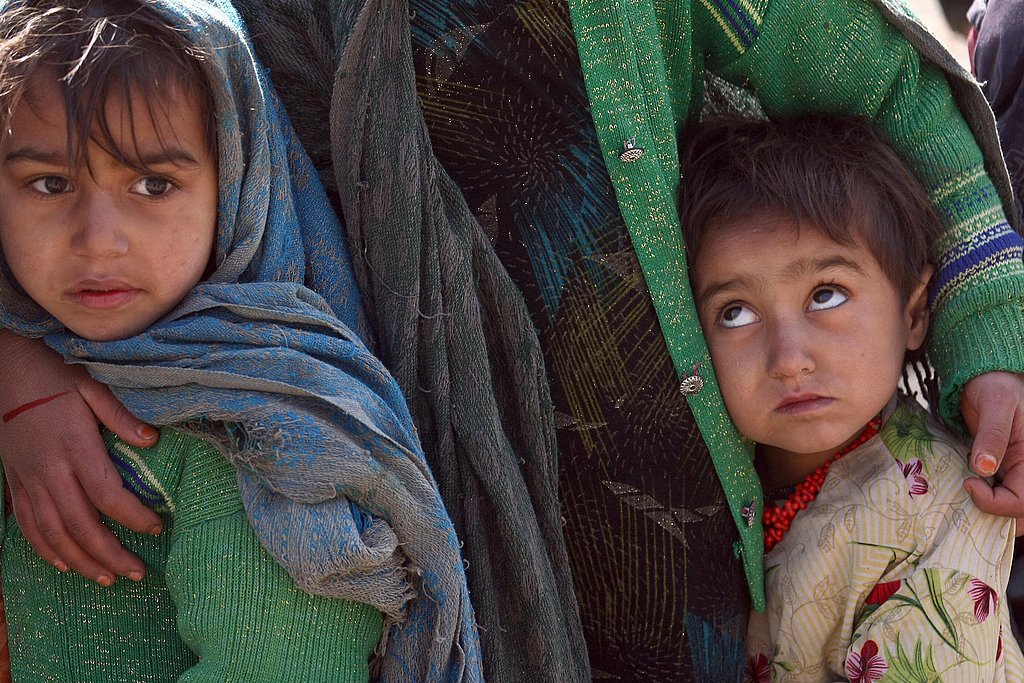Young Afghan children wait in a food line, after a military operation in Dawiatkhel.
