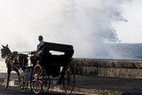 A horse and carriage navigates along the Malecon seafront