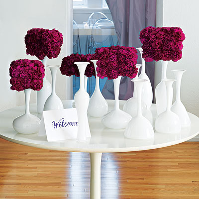 InStyle Weddings created this dramatic display by using carnations in dense arrangements. The contrast between the white vases and the bold, deep hues of the flowers is dramatic and lovely.