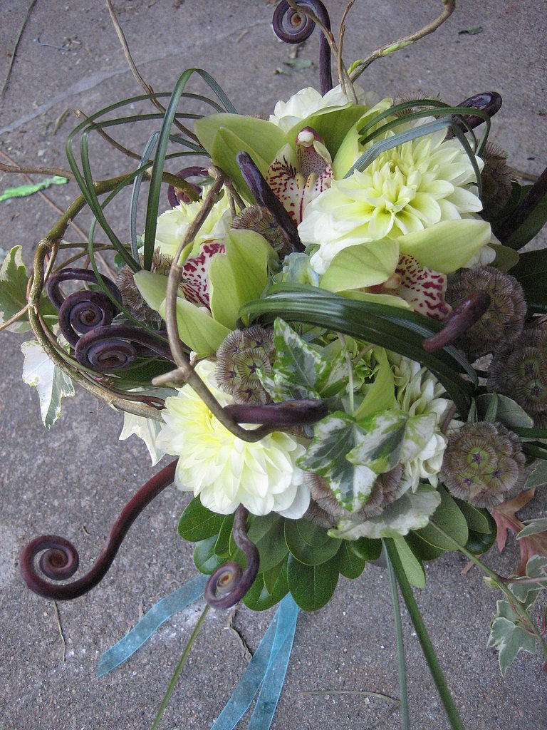 Fiddlehead ferns in a dark purple add an unexpected spiral shape to this bridal bouquet. Source